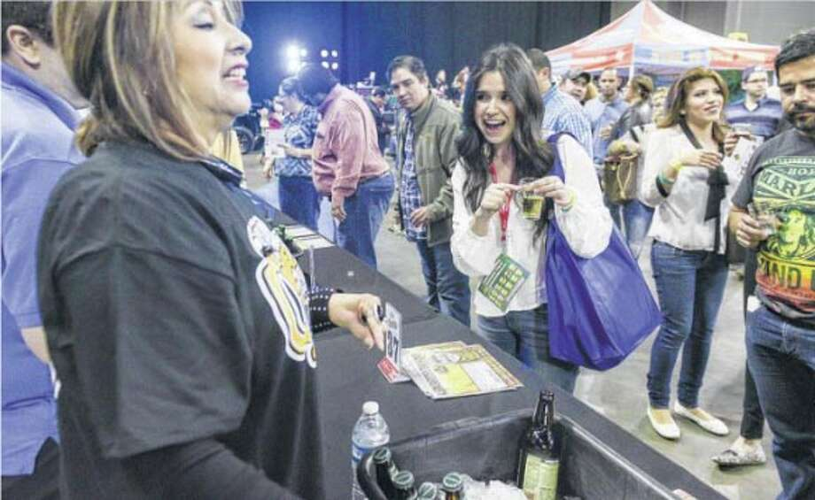 Isa Gomez points to her glass of Austin Eastciders Texas Honey on Saturday night at the Laredo Energy Arena during the 5th Annual Border Beer Fest. Photo: Danny Zaragoza
