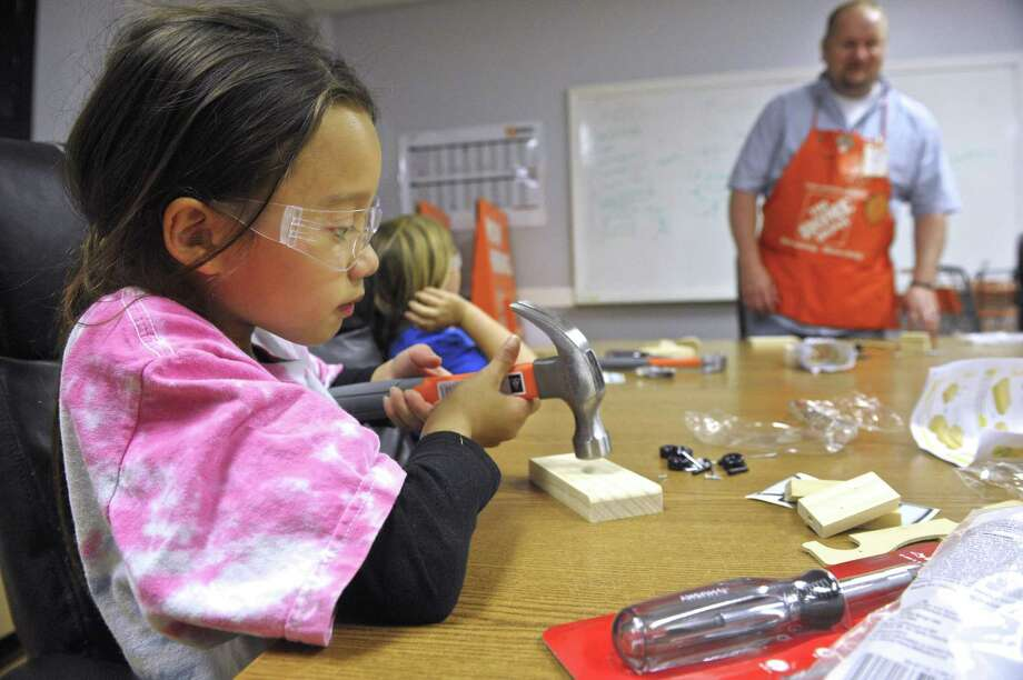At left, Siane Nguyen, 8, hammers in a nail. Photo: H John Voorhees III / Hearst Connecticut Media / The News-Times