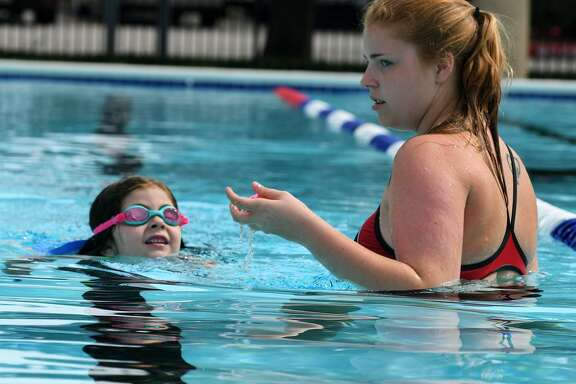 Lifeguard and swim instructor Sasha Brenttinger, 18, right, works with student Tabitha Cains, 5 1/2, during a lesson at the main pool of the D. Bradley McWilliams YMCA on May 23, 2018, which opened for business on May 5 while the reconstruction inside the Y's main building continues. (Jerry Baker/For the Chronicle)