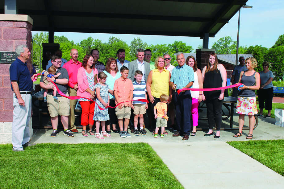 Mark and Sally Speciale, in front, cut the ribbon to open the Nick Ursch Memorial Pavilion Saturday at Leon Corlew Park.