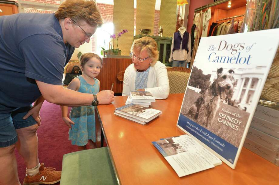 Above, Margaret Reed, author of The Dogs of Camelot, signs a half dozen books for Lisa Lake and her daughter, Evelyn Collier-Lake, during a book signing at L'Armoire in New Canaan  on Tuesday. At right, Reed talks with Westport's Karen Varsano and her daughter, Logan, who was a research assistant for her book. Photo: Alex Von Kleydorff / Hearst Connecticut Media / Norwalk Hour