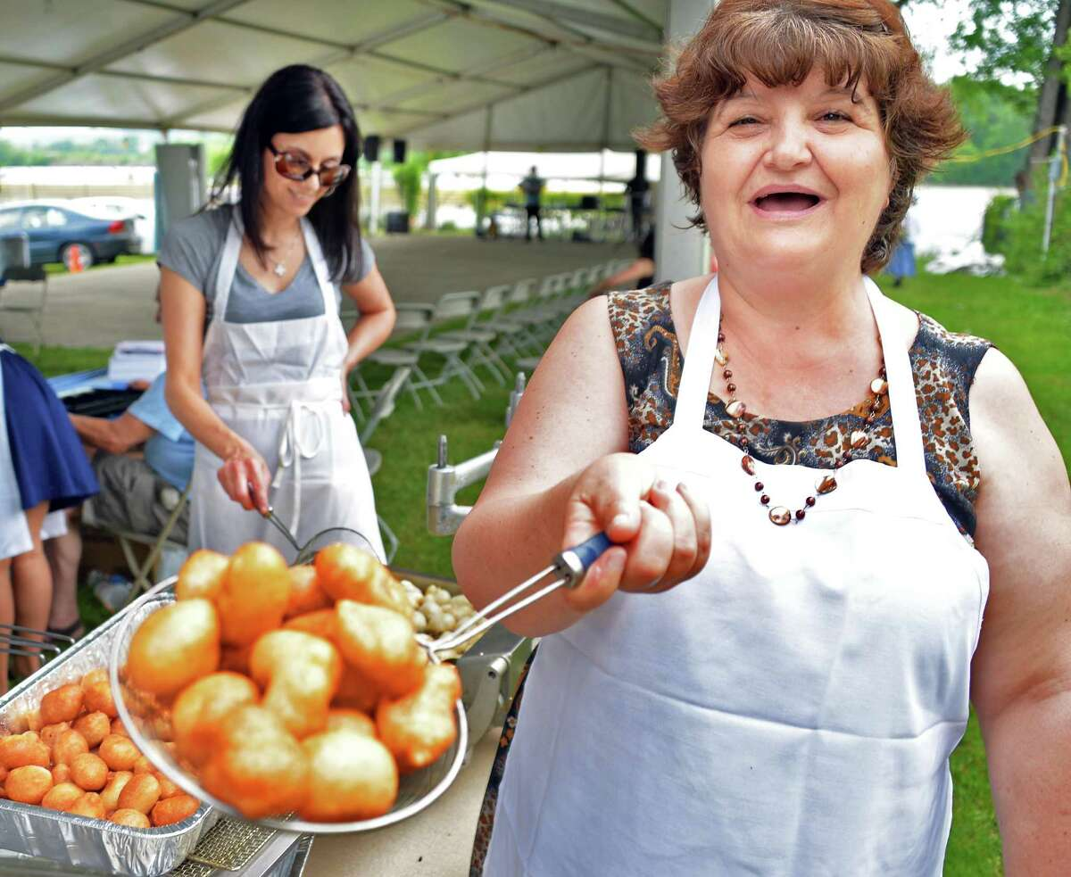 Despina Brosinhan, left, and Soula Oureilidis prepare Loukoumathis, traditional Greek fried dough topped with a sweet syrup, at the annual Greek Festival at St. Basil's Greek Orthodox Church on River Street in Troy, NY, Saturday June 1, 2013. The festival continues on Sunday. (John Carl D'Annibale / Times Union)
