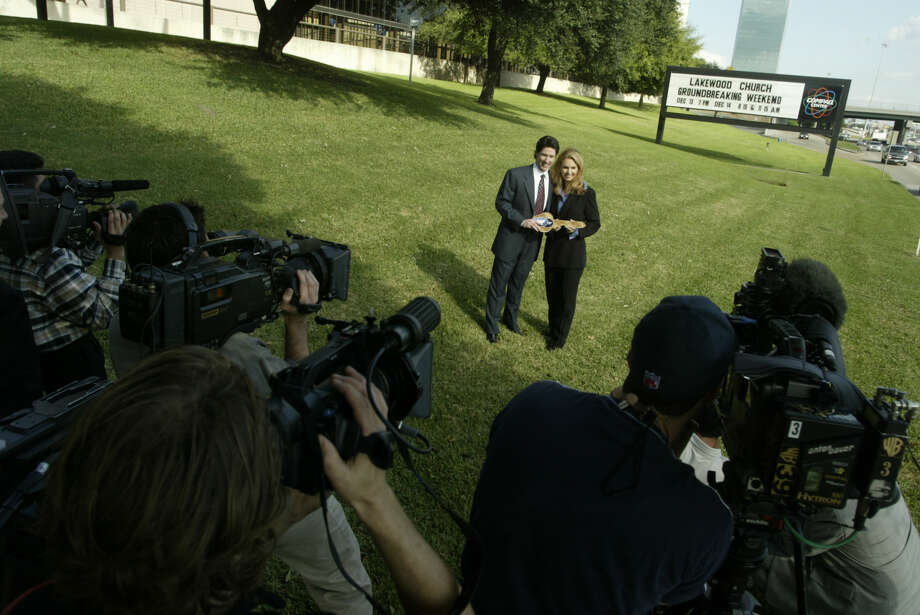 Lakewood Church Pastor Joel Osteen and his wife, Victoria, pose for pictures in front of the Compaq Center on Dec. 1, 2003, as the city of Houston turned over the keys to the church. (Houston Chronicle File)