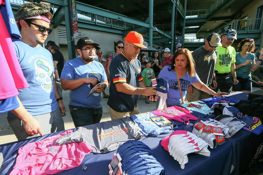 Jerry Barrazo (from left), Jorge Lozano, Ruben Hernandez and Diane Hernandez look over Flying Chanclas shirts and caps during the Flying Chanclas' game with Tulsa at Wolff Stadium on Thursday, May 24, 2018.  MARVIN PFEIFFER/mpfeiffer@express-news.net Photo: Marvin Pfeiffer, San Antonio Express-News / Express-News 2018