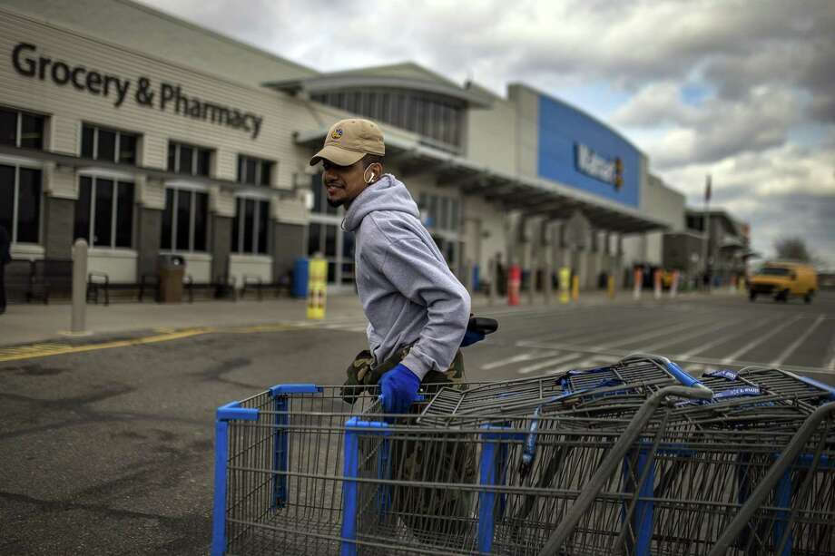 A worker collects shopping carts at a Walmart in Secaucus, N.J., March 14, 2018. Joining a growing list of companies that are helping employees pay for higher education as a perk in a tight labor market, Walmart announced on May 30 that it would begin offering subsidized tuition toward business or supply chain management degrees for its 1.4 million workers in the United States. Photo: ANDRES KUDACKI /NYT / NYTNS