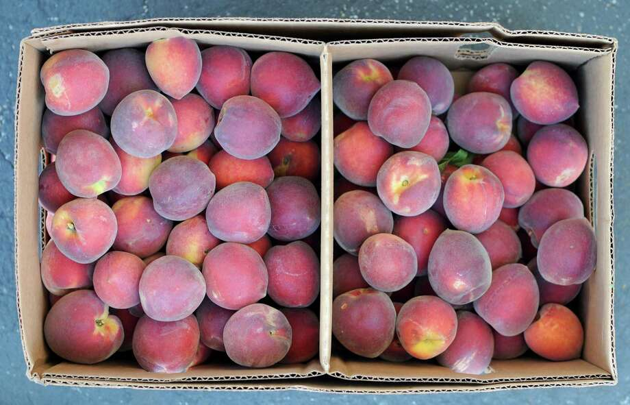 Baskets of ripe Texas Hill Country peaches can now be found at area farmers markets. Photo: Paul Stephen / San Antonio Express-News