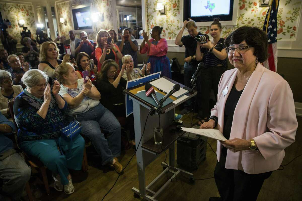 In this photo taken May 22, 2018, gubernatorial candidate and former Dallas County Sheriff Lupe Valdez, right, speaks after her runoff win at a Democratic party celebration at Ellen's in Dallas. Valdez owes $12,000-plus in overdue property taxes on seven properties, a previously unreported shortfall that could prove embarrassing as she tries to unseat Republican Greg Abbott in November. The Houston Chronicle reports that Valdez's campaign acknowledges that she owes back property taxes, but is paying them back in installments. (Ashley Landis/The Dallas Morning News via AP)