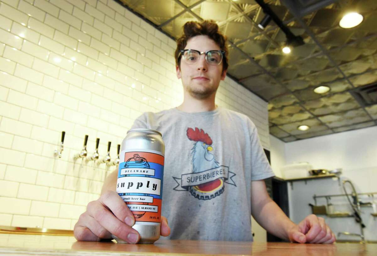 Colin Pratt, proprietor of Delaware Supply, holds a beer that was canned on the premises on Friday, May 25, in Albany, N.Y. (Will Waldron/Times Union)