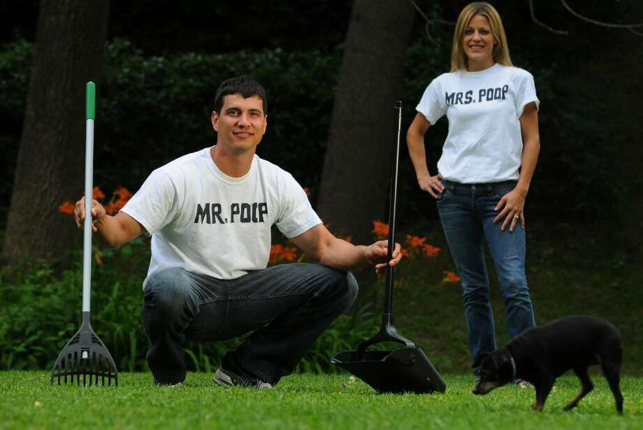 Luke Gladue holds the implements of his new business for cleaning up dog excrement from the yards of his clients, with his wife Terri and their dog Abby at their Clifton Park home on Thursday, July 1, 2010. (Philip Kamrass / Times Union ) Photo: PHILIP KAMRASS