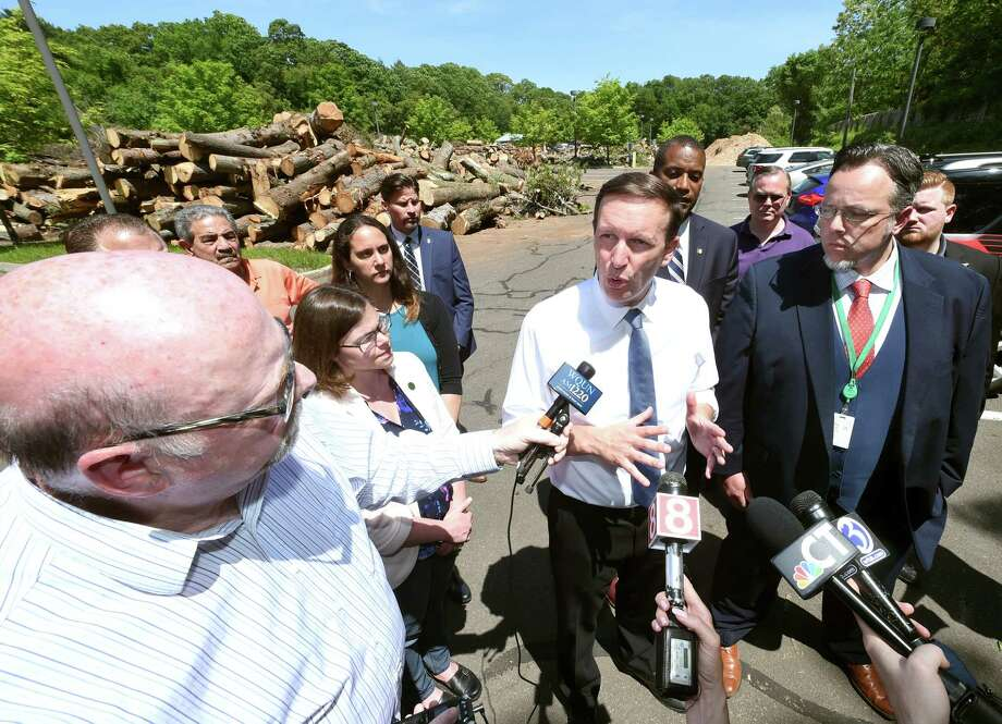 During a tour of storm damage in Hamden, U.S. Senator Chris Murphy (center) speaks with the media concerning the damage in the parking lot donated by Quinnipiac University for storm debris on Whitney Ave. in Hamden on May 30, 2018.  At right is Hamden Mayor Curt Leng. Photo: Arnold Gold, Hearst Connecticut Media / New Haven Register