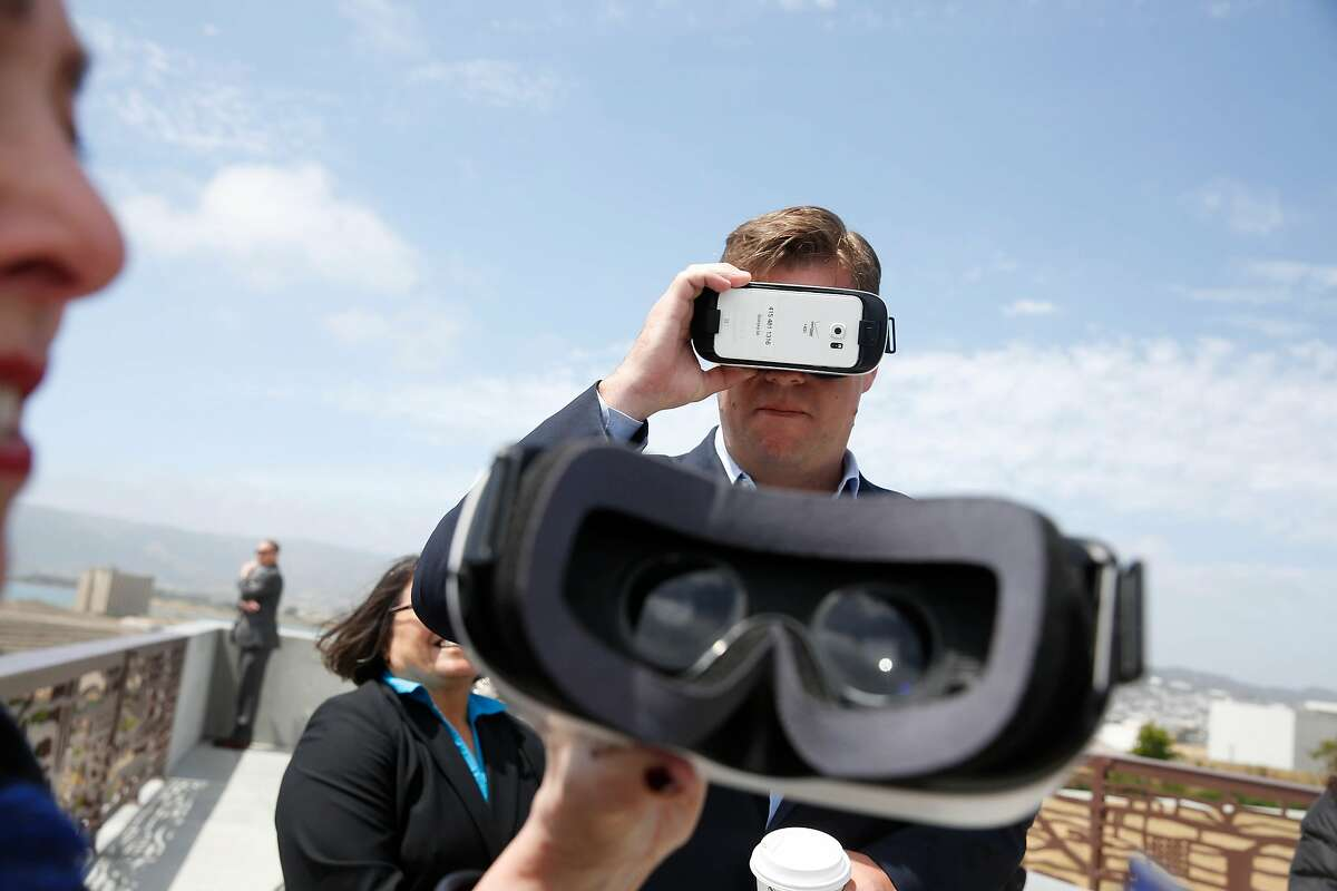 Mayor Mark Farrell (right) looks at past and future views of the shipyard on a virtual reality headset during a tour of Parcel A on Wednesday, May 30, 2018 in San Francisco, Calif.