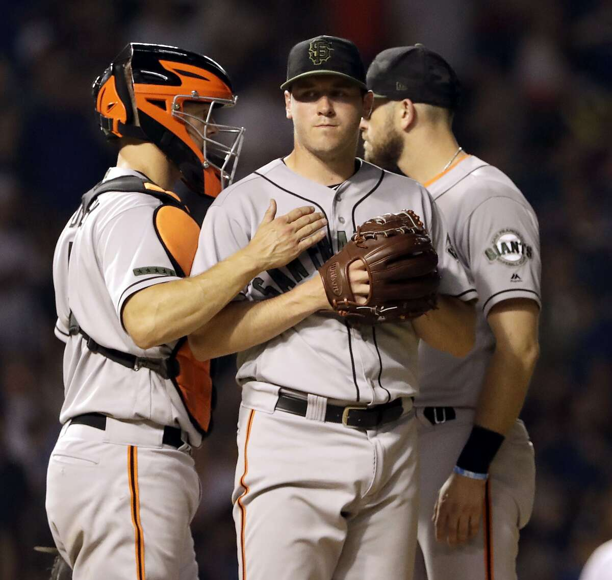 San Francisco Giants starting pitcher Ty Blach, center, reacts as he listens to catcher Nick Hundley, left, and third baseman Evan Longoria during the fourth inning of a baseball game against the Chicago Cubs in Chicago, Sunday, May 27, 2018. (AP Photo/Nam Y. Huh)