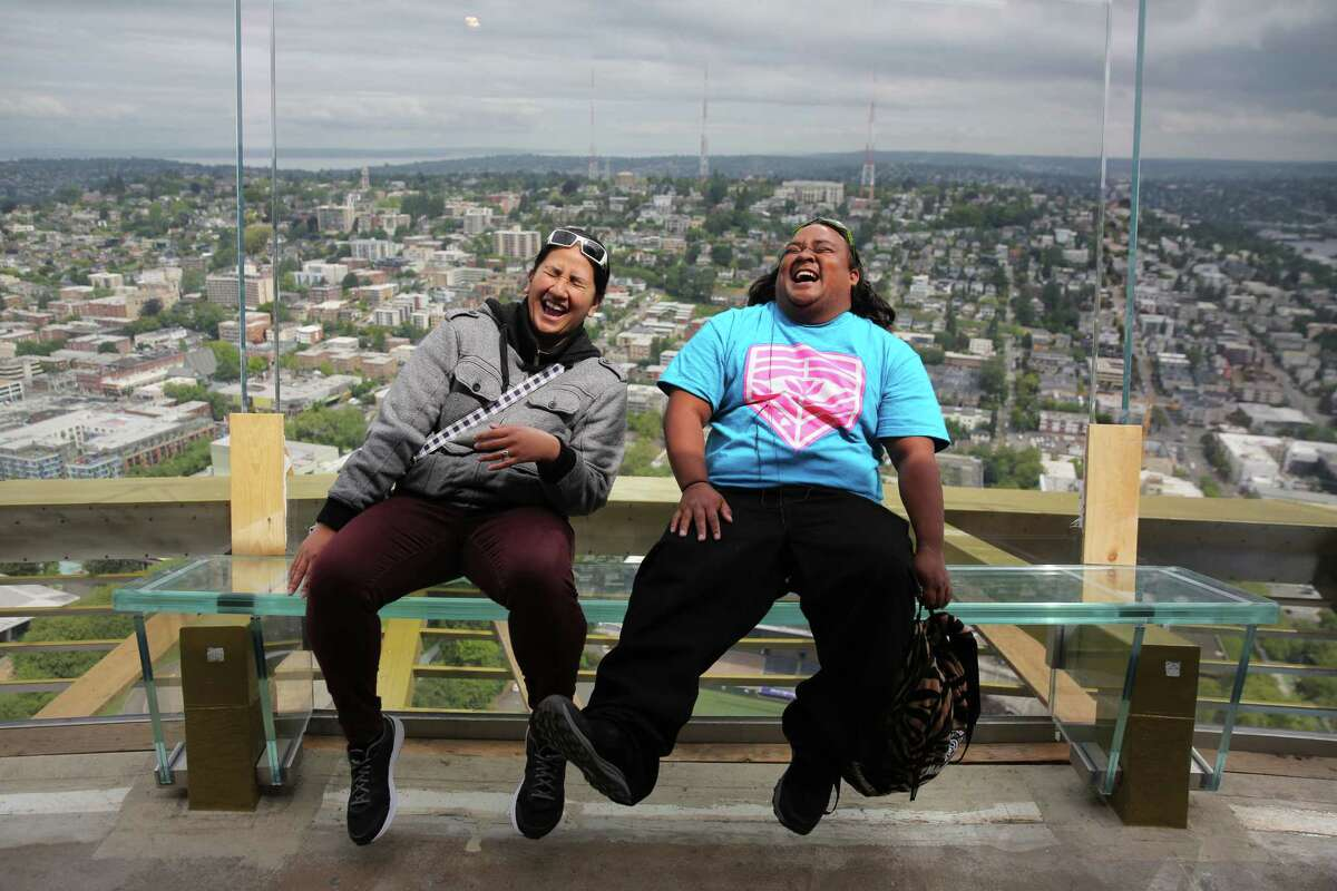 Jessica Longboy and Kalei Amion, who are visiting Seattle from Hawaii, laugh as they nervously sit back against the new glass walls of the Space Needle observation deck, Wednesday, May 30, 2018. The new angled glass benches and barrier walls give visitors a thrill.