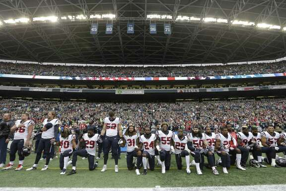 Houston Texans players kneel and stand on Oct. 29 during the singing of the national anthem before an NFL football game against the Seattle Seahawks, in Seattle. A reader disagrees with a columnist on this, and defends him.