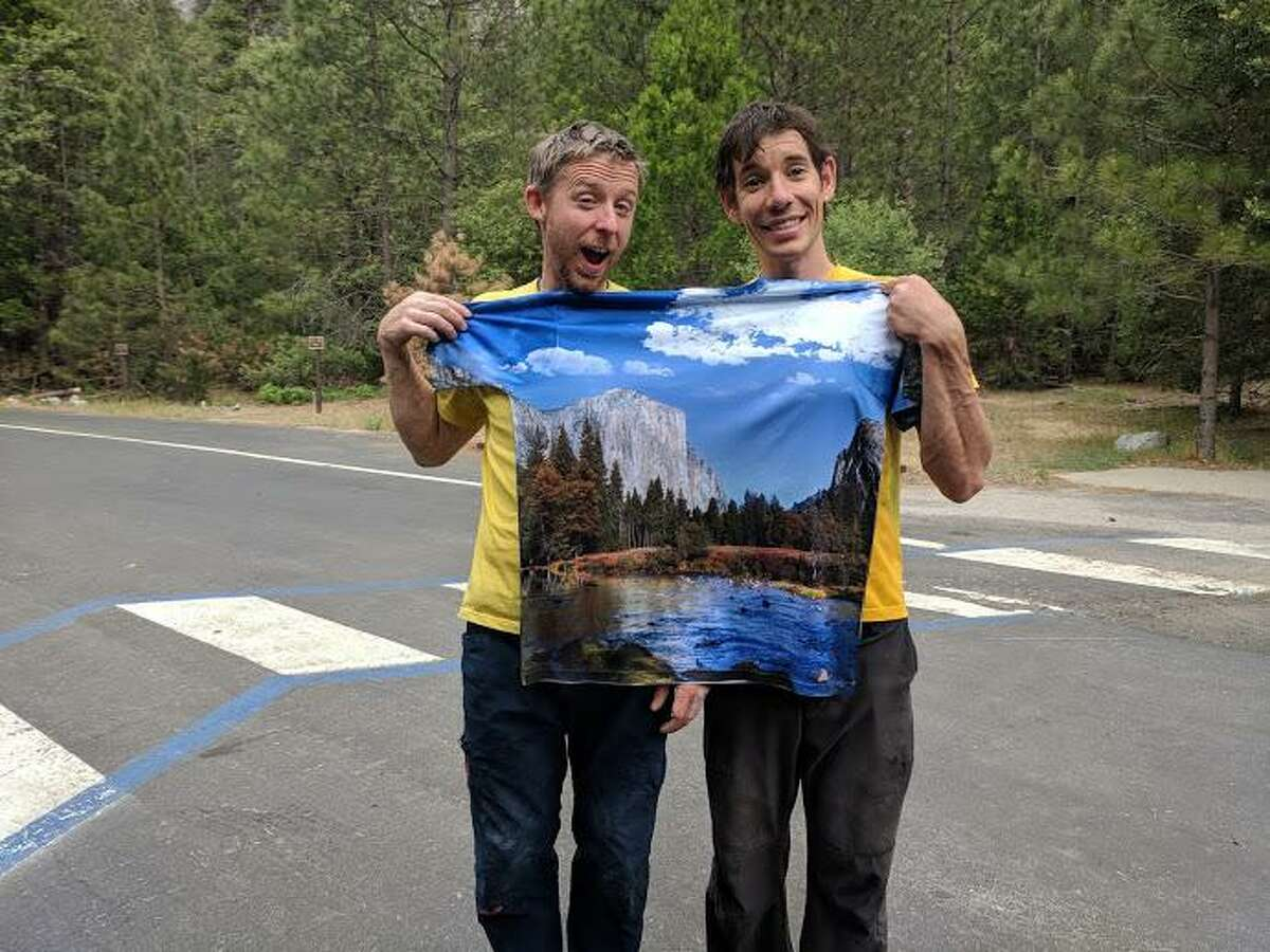 Tommy Caldwell, left, and Alex Honnold, right, hold a t-shirt with an image of the mountain they just climbed as they celebrate their record on the Nose route of El Capitan.