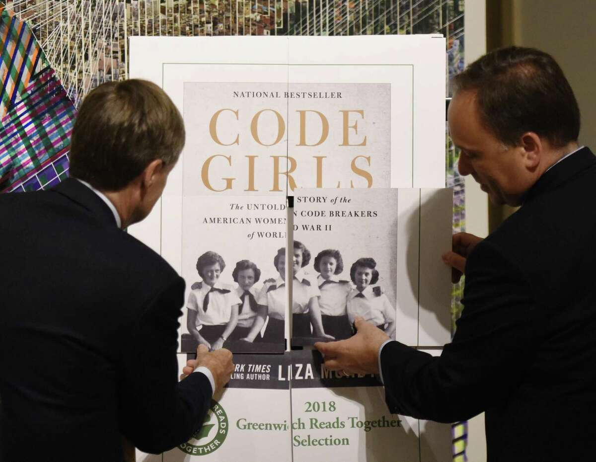 """Greenwich Library Board of Trustees President Rob Marks, left, and First Selectman Peter Tesei reveal the 2018 Greenwich Reads Together book, """"Code Girls,"""""""