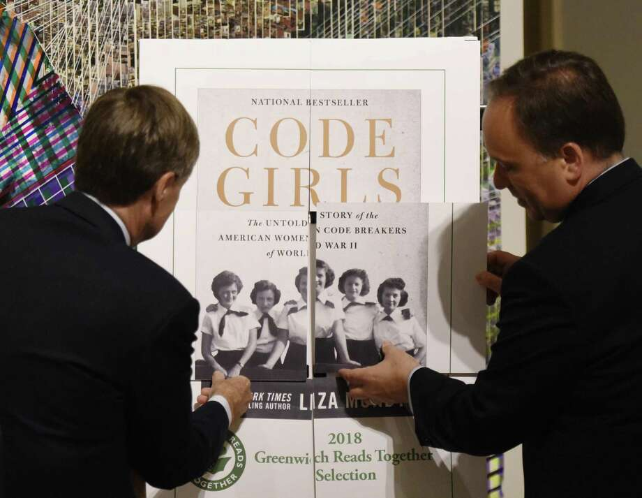 "Greenwich Library Board of Trustees President Rob Marks, left, and First Selectman Peter Tesei reveal the 2018 Greenwich Reads Together book, ""Code Girls,"" Photo: Tyler Sizemore / Hearst Connecticut Media / Greenwich Time"