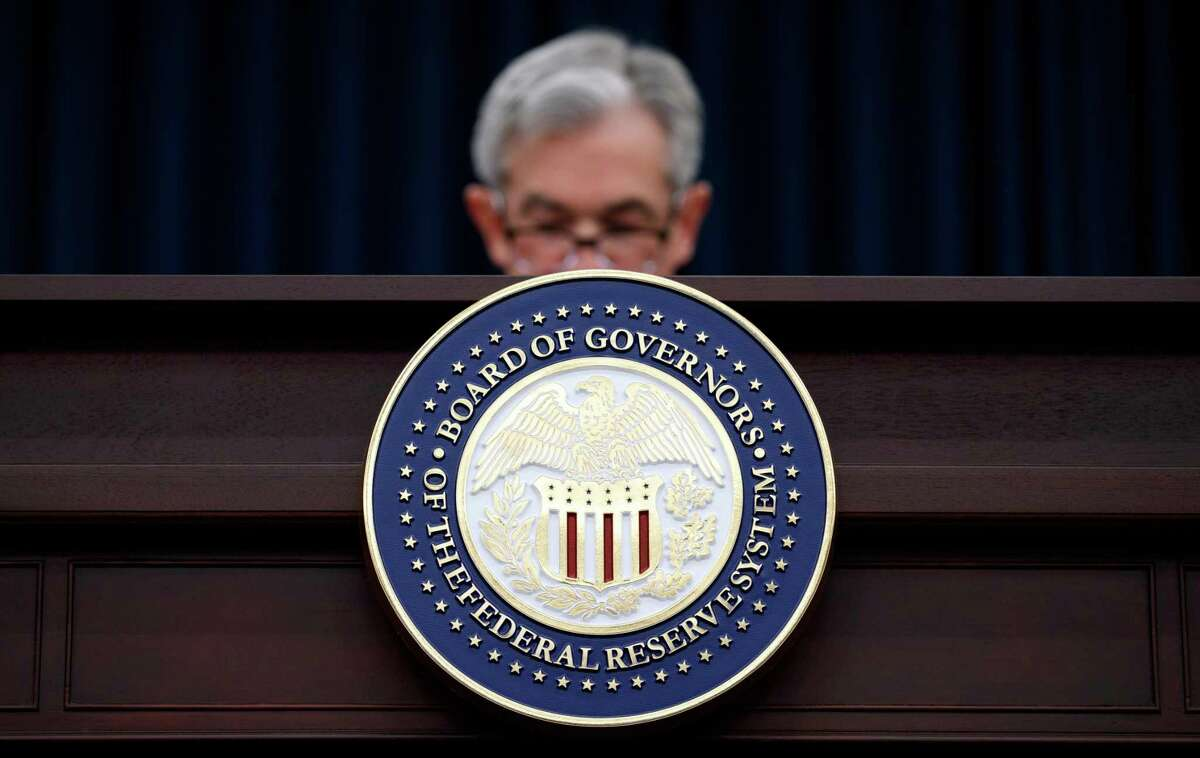 In this March 21, 2018, file photo, Federal Reserve Chairman Jerome Powell looks to his notes as he speaks during a news conference following the Federal Open Market Committee meeting in Washington. Federal bank regulators on Wednesday unveiled a sweeping plan to soften the Volcker Rule, opening the door for banks to resume some trading activities restricted as part of the 2010 Dodd-Frank law.