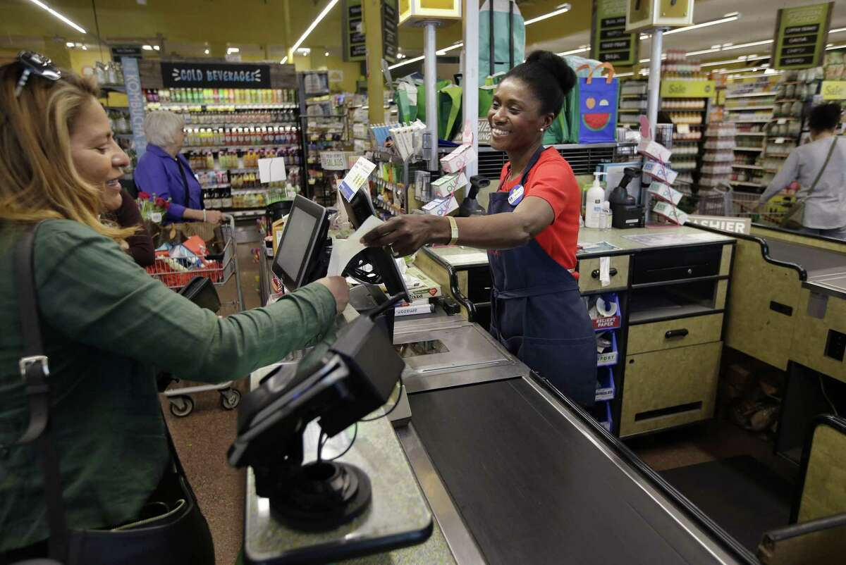 In this May 8, 2018, photo, Nadine Vixama, who emigrated from Haiti eight years ago, works as a cashier at a Whole Foods in Cambridge, Mass. Vixama has taken English classes and a program in store and customer service basics developed by the National Retail Federation trade group to gain work skills in retail.