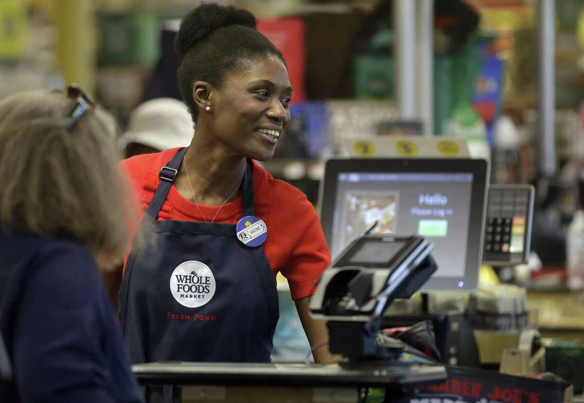 In this May 8, 2018, photo, Haitian immigrant Nadine Vixama works as a cashier at a Whole Foods in Cambridge, Mass. Vixama has taken English classes and a program in store and customer service basics launched by the National Retail Federation trade group though a local organization that helps people gain work skills. Ive learned to treat customers in a better way ... how to keep pace with them, Vixama said.