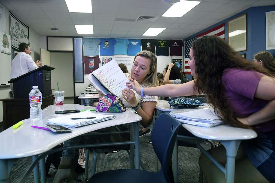 Melissa Reeves, 17, center, and her Kingwood High School junior classmate Marissa Amar, 17, right, the KHS Student Body President, check their notes during an AP Dual Credit History class taught by teacher Mark Scalia, left, during their first day back on the KHS campus for the 2017-2018 schoool year on Monday, March 19, 2018. (Photo by Jerry Baker/Freelance)