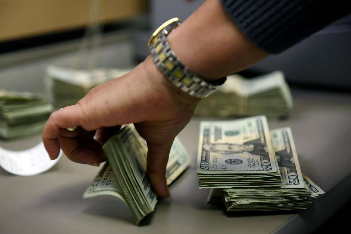 A cashier counts a marijuana business owner's cash tax payment at the California Department of Tax and Fee Administration in Oakland, CA, on Monday November 27, 2017.