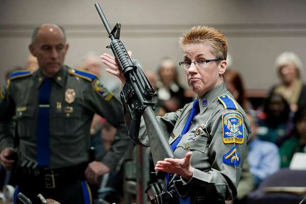 FILE - In this Jan. 28, 2013, file photo, firearms training unit Detective Barbara J. Mattson, of the Connecticut State Police, holds up a Bushmaster AR-15 rifle, the same make and model of gun used by Adam Lanza in the Sandy Hook School shooting, during a hearing of a legislative subcommittee, at the Legislative Office Building in Hartford, Conn. Lawyers for the company that made the rifle Lanza used at Sandy Hook Elementary School in 2012 are expected to ask a Connecticut judge Monday, Feb. 22, 2016, to dismiss a wrongful death lawsuit filed by families of some of the massacre victims. Freedom Group, the Madison, North Carolina parent company of AR-15 maker Bushmaster Firearms, says it�s protected by a 2005 federal law that shields gun manufacturers from most lawsuits over criminal use of their products. (AP Photo/Jessica Hill, File)