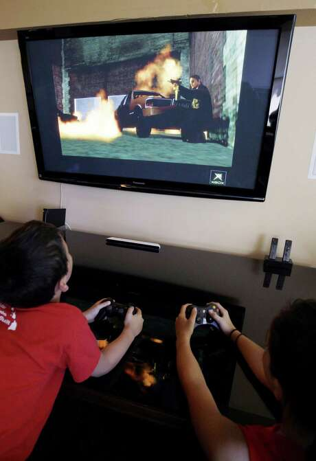Two boys, ages 9 and 13, play  Grand Theft Auto IV in Los Altos, Calif. Photo: Paul Sakuma, STF / Associated Press / AP