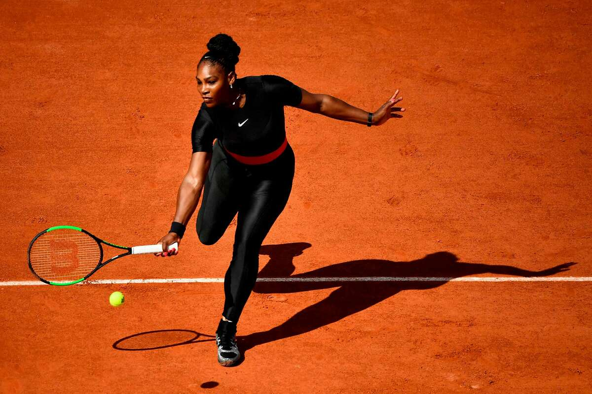 """(FILES) In this file photograph taken on May 29, 2018, Serena Williams of the US plays a forehand return to Czech Republic's Kristyna Pliskova during their women's singles first round match on day three of The Roland Garros 2018 French Open tennis tournament in Paris. Serena Williams hit the headlines for her eye-catching, body-hugging black catsuit at the French Open, an outfit she described as """"fun and functional"""", helping her prevent a return of the blood clots which put her life in danger after giving birth last year. / AFP PHOTO / CHRISTOPHE SIMONCHRISTOPHE SIMON/AFP/Getty Images"""