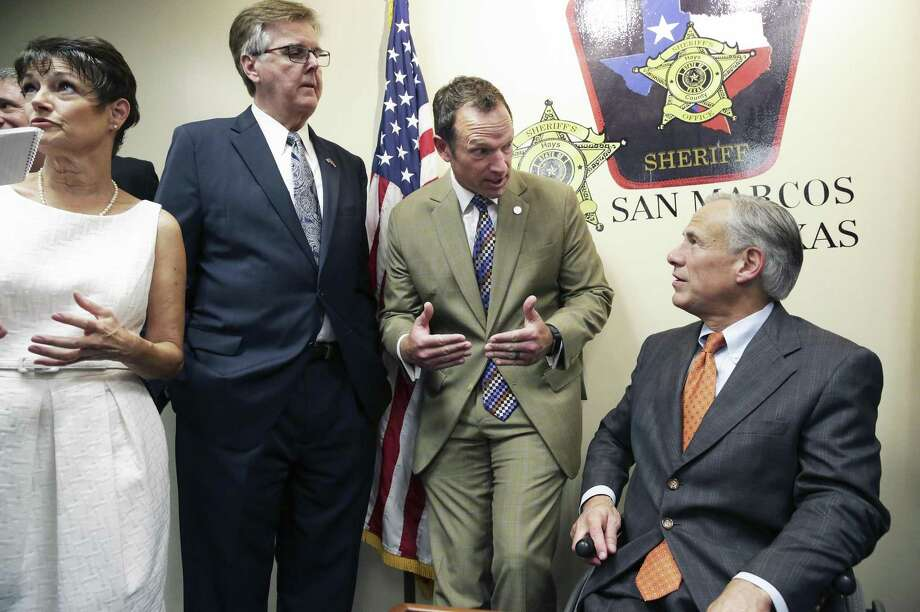Gov. Greg Abbott discusses plans with Sen. Donna Campbell, R-New Braunfels; Lt. Gov. Dan Patrick and Rep. Jason Isaac, R-Blanco, after he reveals his school safety proposals at a Wednesday news conference at the Hays County Law Enforcement Center in San Marcos. He also presented his plan earlier in the day at Dallas. . Photo: Tom Reel /San Antonio Express-News / 2017 SAN ANTONIO EXPRESS-NEWS