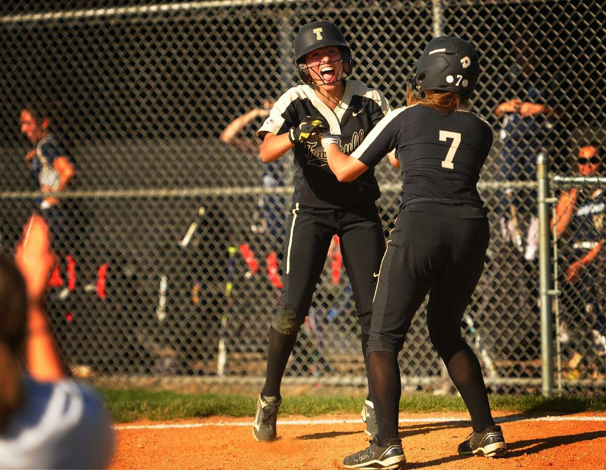 Trumbull players Maggie Coffin, left, and Ava Dunn celebrate at home plate after scoring two runs in the bottom of the 7th inning to give their team a 5-4 victory over Middletown in the second round of the CIAC girls softball tournament at Trumbull High School on Wednesday.