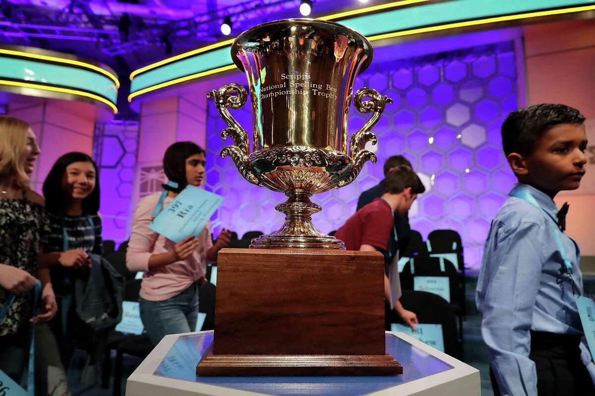 Competitors walk past the championship trophy on display Wednesday during the third round of the 91st Scripps National Spelling Bee at the Gaylord National Resort and Convention Center in National Harbor, Maryland.