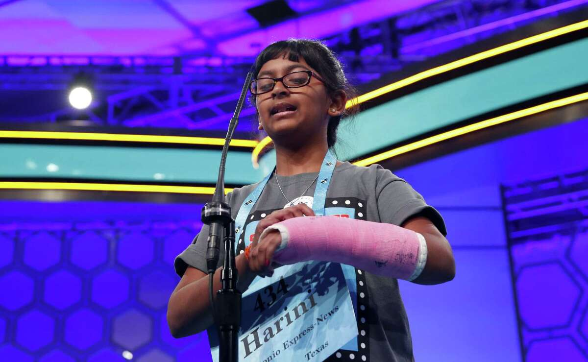Harini Logan, 10, from San Antonio, uses her cast to spell her word Tuesday during the 2nd Round of the Scripps National Spelling Bee. On Wednesday, she missed her word, but she still plans on watching the finals.