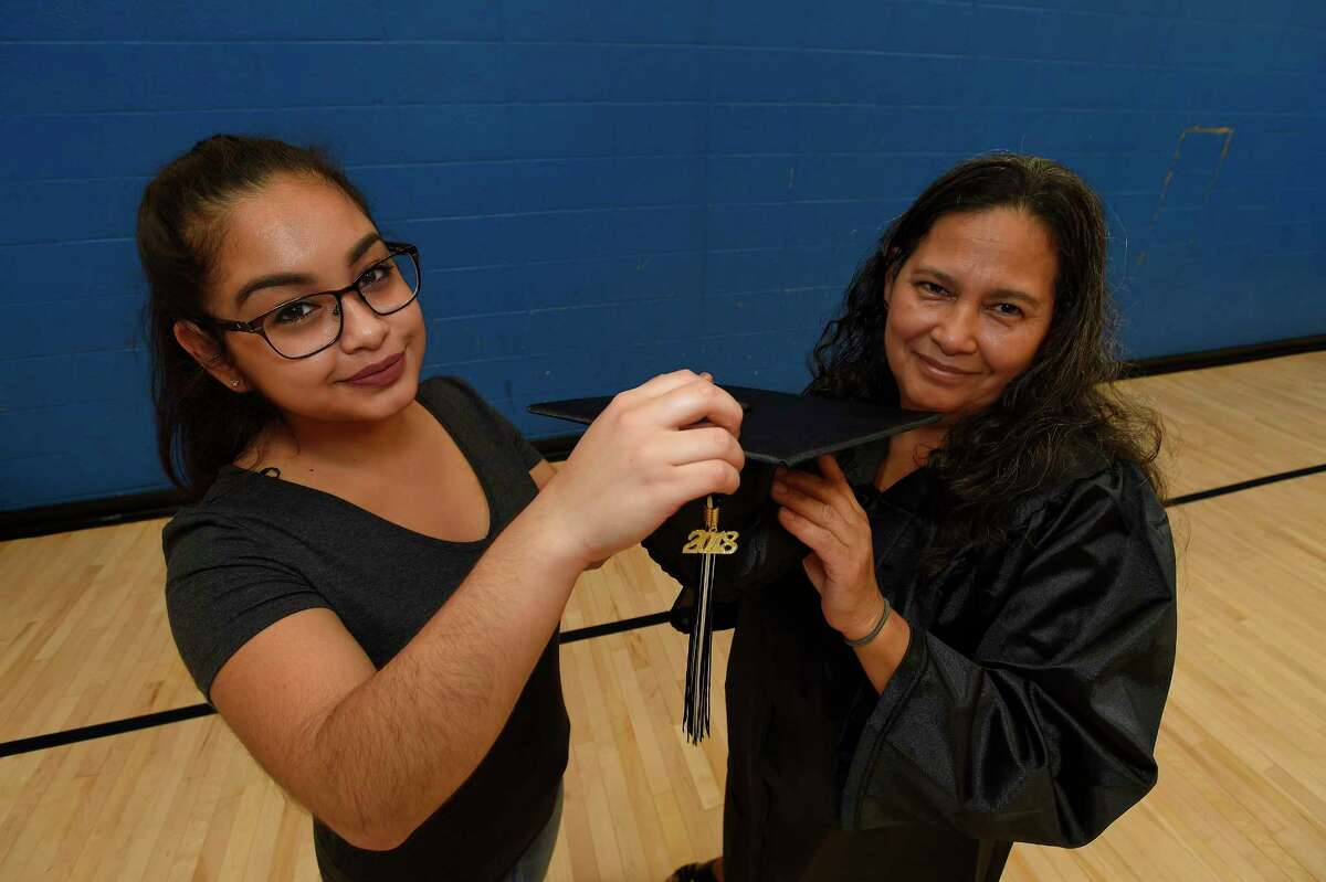 Gabriela Marroquin, 18, helps her mother Norma Marroquin prepare for the Stamford Public Schools Adult & Continuing Education graduation ceremony at Cloonan Middle School on May 30, 2018 in Stamford, Connecticut.