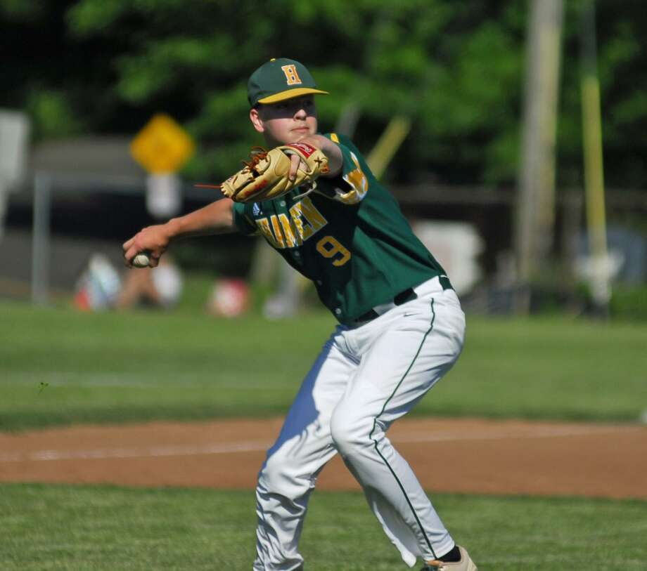 Hamden's Jacob Michaud throws to first base during a Class LL playoff game against Ridgefield on Wednesday. Photo: Ryan Lacey /Hearst Connecticut Media