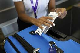 FILE- In this July 12, 2016, file photo, a Delta Air Lines employee places an RFID-enabled baggage tag on a passenger's checked bag at Baltimore-Washington International Thurgood Marshall Airport in Linthicum, Md. If an airline forces a passenger off a flight for lack of space, under federal rules the passenger is entitled to cash compensation, not just a voucher, and a seat on a later flight. Bumped passengers whose travel is delayed for at least an hour are entitled to up to $1,350 in compensation, with the amount based on the length of the delay and the one-way price of the ticket. Delta vouchers can be applied to government taxes. (AP Photo/Patrick Semansky, File)