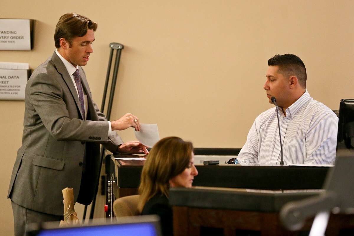Prosecutor Josh Somers (left) shows a photo of the body of Jose Luis Menchaca to Dennis Austin on the witness stand during the third day of testimony in the retrial of Daniel Lopez in the 379th state District Court at the Cadena-Reeves Justice Center on Wednesday, May 30, 2018. Lopez is accused with two others of beating, dismembering and burning body parts of Menchaca, his girlfriend's cousin, in retaliation over a stabbing in a drug deal gone bad. MARVIN PFEIFFER/mpfeiffer@express-news.net