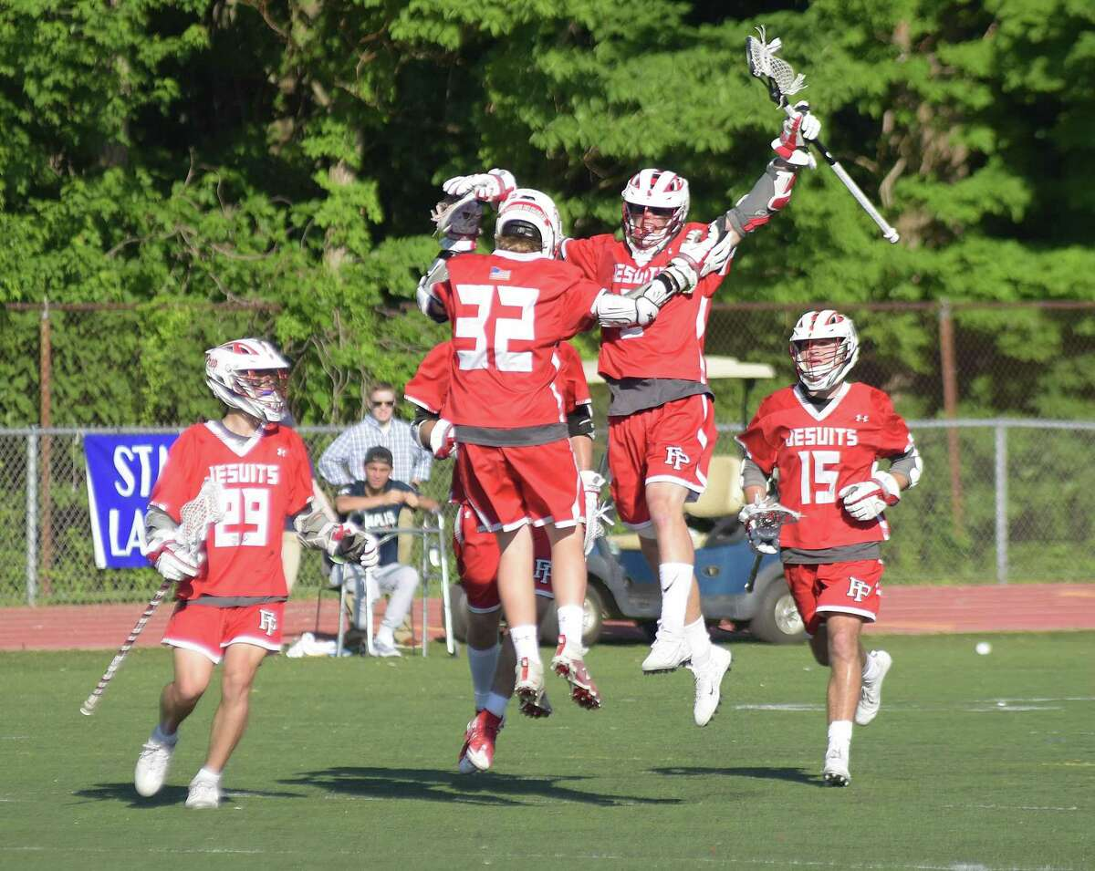 Fairfield Prep players, from left, Mason Reale, Patrick McAleavey, Timothy Rohach and Peter Kavanaugh come together to celebrate a goal during the Jesuits 11-10 Class L state tournament overtime win over Staples in Westport on Wednesday.