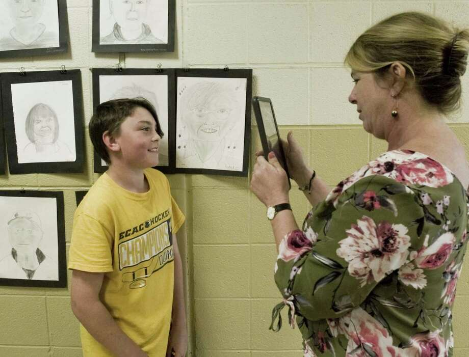 Scotts Ridge Middle School seventh-grader Henry Idone stands with the portrait he drew of a Founders Hall member as school library assistant Emily Shiller gets a picture. Portraits are displayed on the school hallway walls. Wednesday, May 30, 2018 Photo: Scott Mullin / For Hearst Connecticut Media / The News-Times Freelance