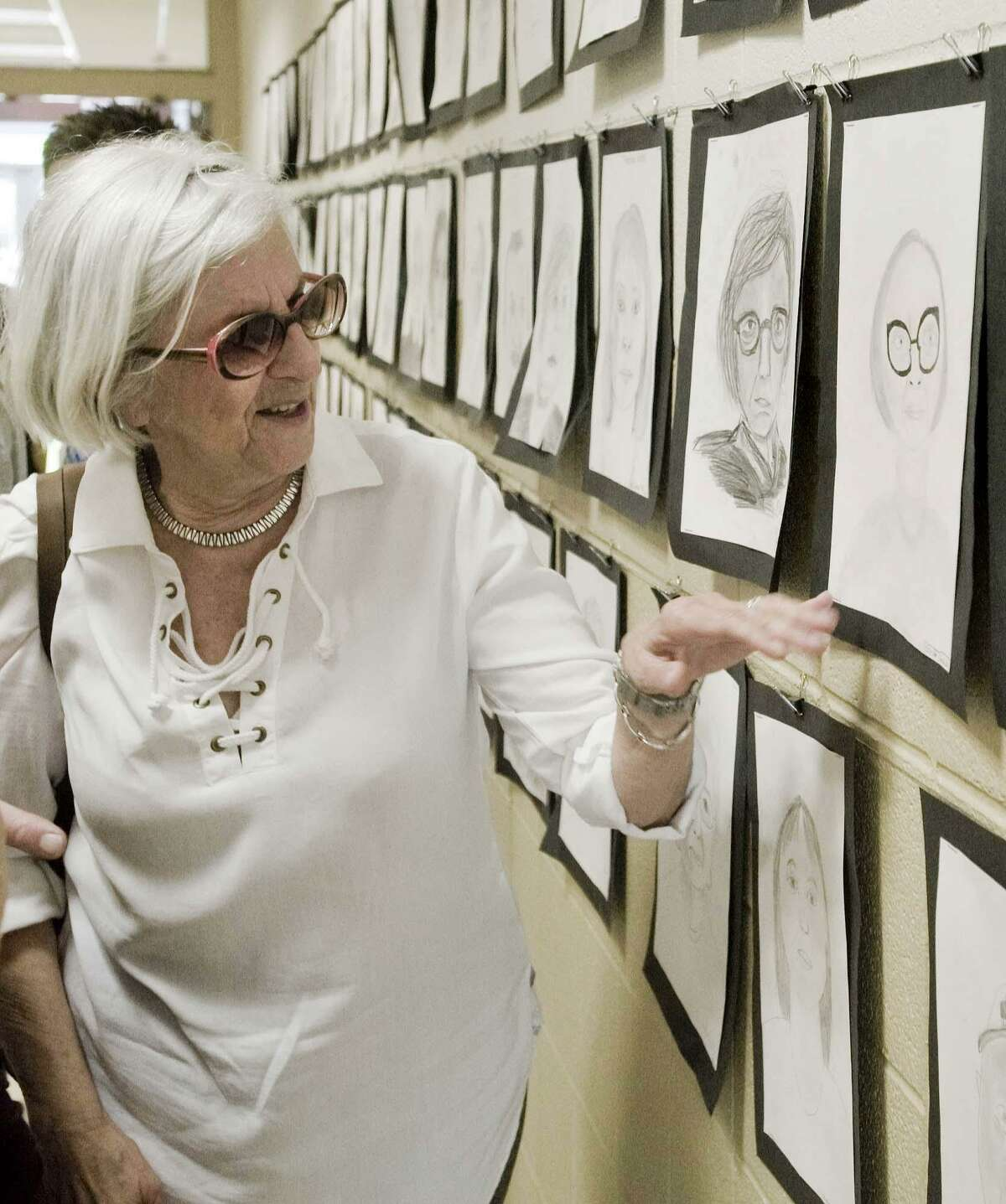 Founders Hall member Clotilde Farrell looks at her portrait drawn by a Scotts Ridge Middle School seventh-grader. Portraits are displayed on the school hallway walls. Wednesday, May 30, 2018