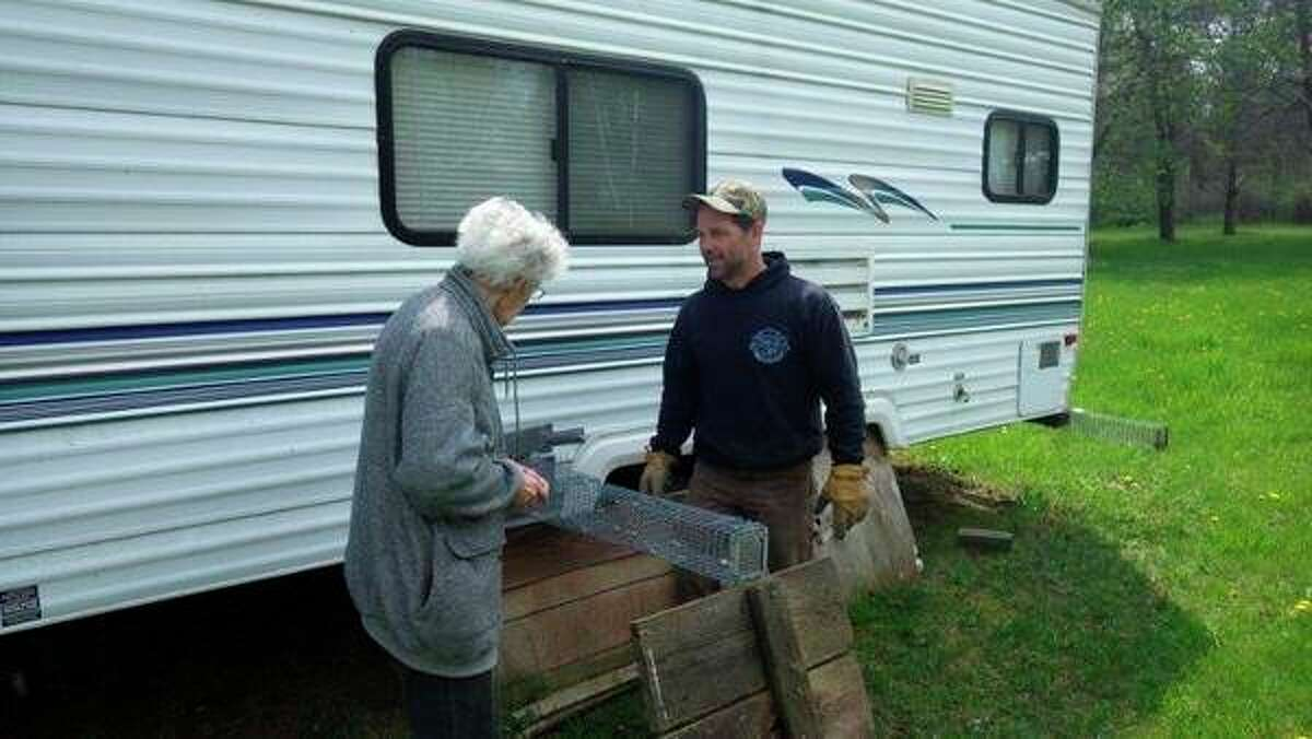 'Critter-Gitter' Chad Seleyexplainsto a homeowner his method ofeliminating red squirrels from a fifth-wheel camper. (Tom Lounsbury/Hearst Michigan)