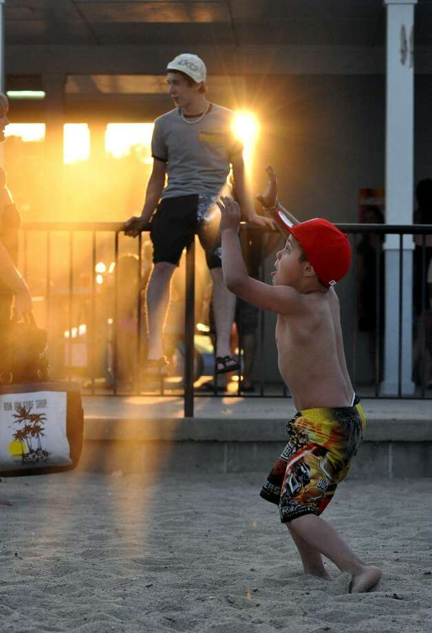 Jayden Perez, 6, of Fairfield catches a ball as sunlight beams through the pavilion at Jennings Beach during the annual Fairfield fireworks on Sunday, July 4, 2010. Photo: Amy Mortensen / Connecticut Post Freelance