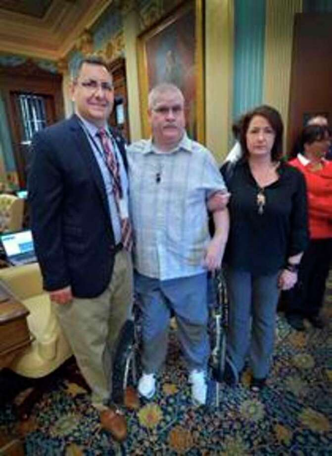 Sen. Jim Stamas, left, hosted John and Dawn Szymanski at the state capitol for the Michigan Senate's Annual Memorial Day Service, which honored Michigan's fallen soldiers. The Szymanskis are the parents of Marine Lance Cpl. Steven J. Szymanski, who was killed in the line of duty at Fort Bragg in 2014. (photo provided)