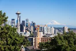 A classic view of Seattle downtown district with the famous Space Needle tower and the Mount Rainier snow covered mountain in the background in Washington state, USA