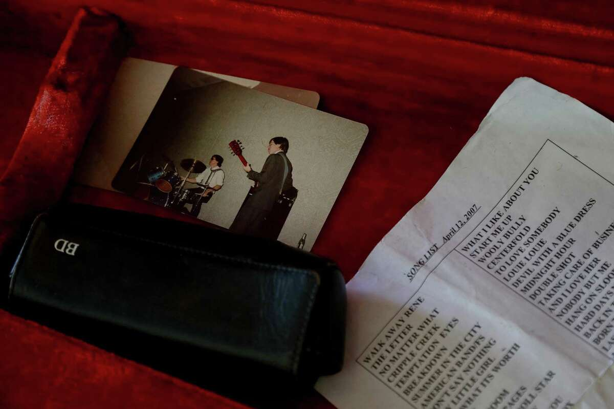 A photograph and a set list from 2007 rest inside David Mitcham's guitar case, during Death by Injection's annual performance at St. Francis de Sales Catholic Church.