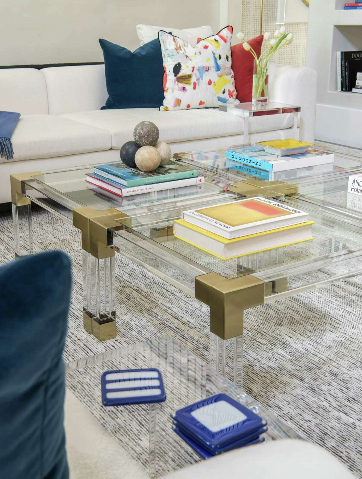 Four Jonathan Adler acrylic tables with brass corners combine for a large cocktail table int he family room.