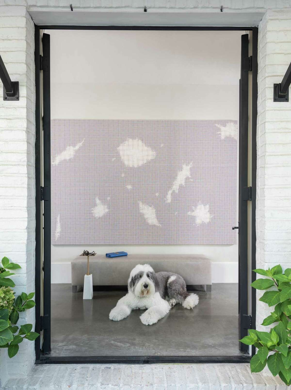 Rocky, the family's old English sheepdog, greets guests in the foyer.