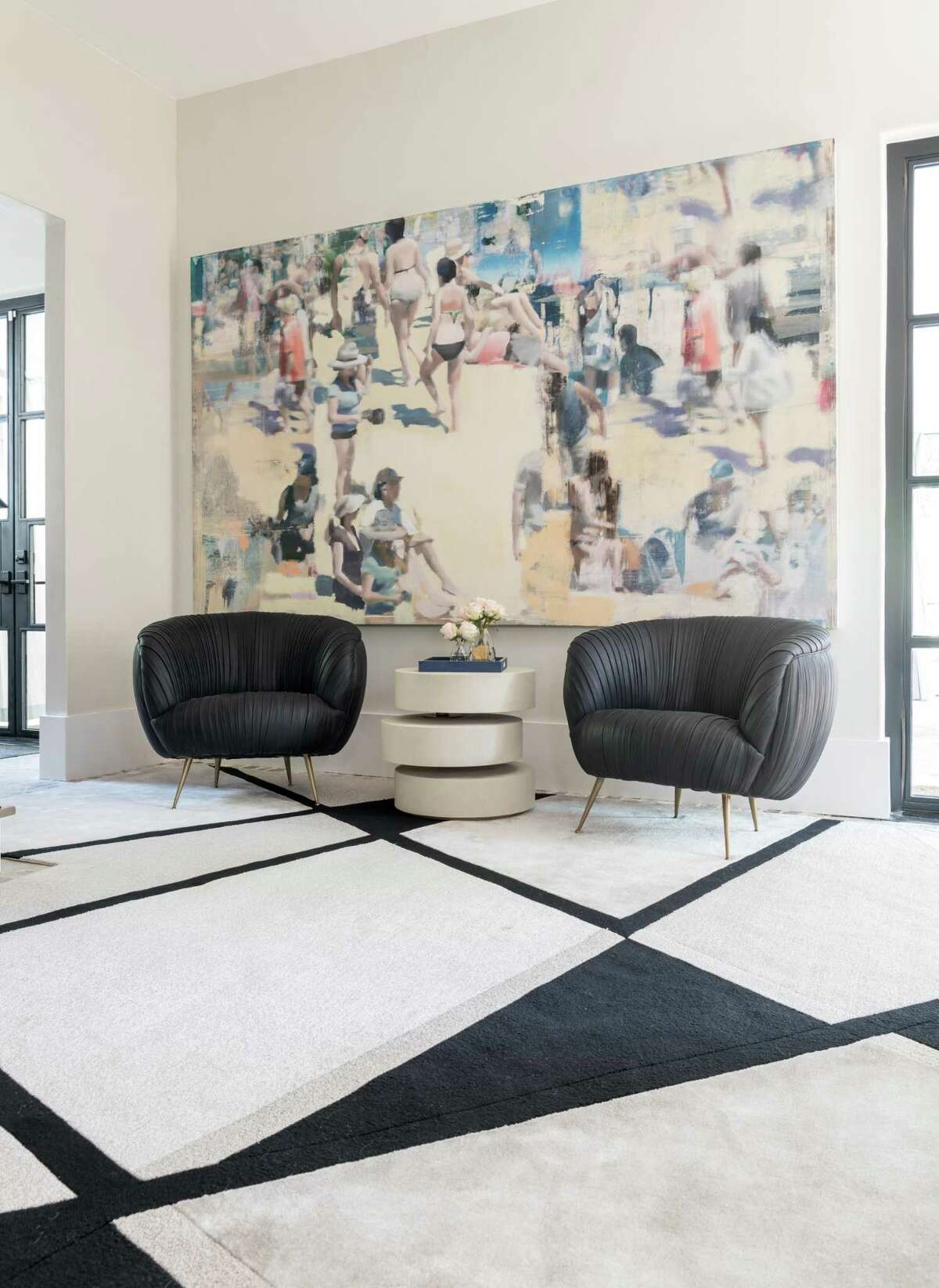 A large piece of art and two Kelly Wearstler chairs cover one wall in the breakfast room.