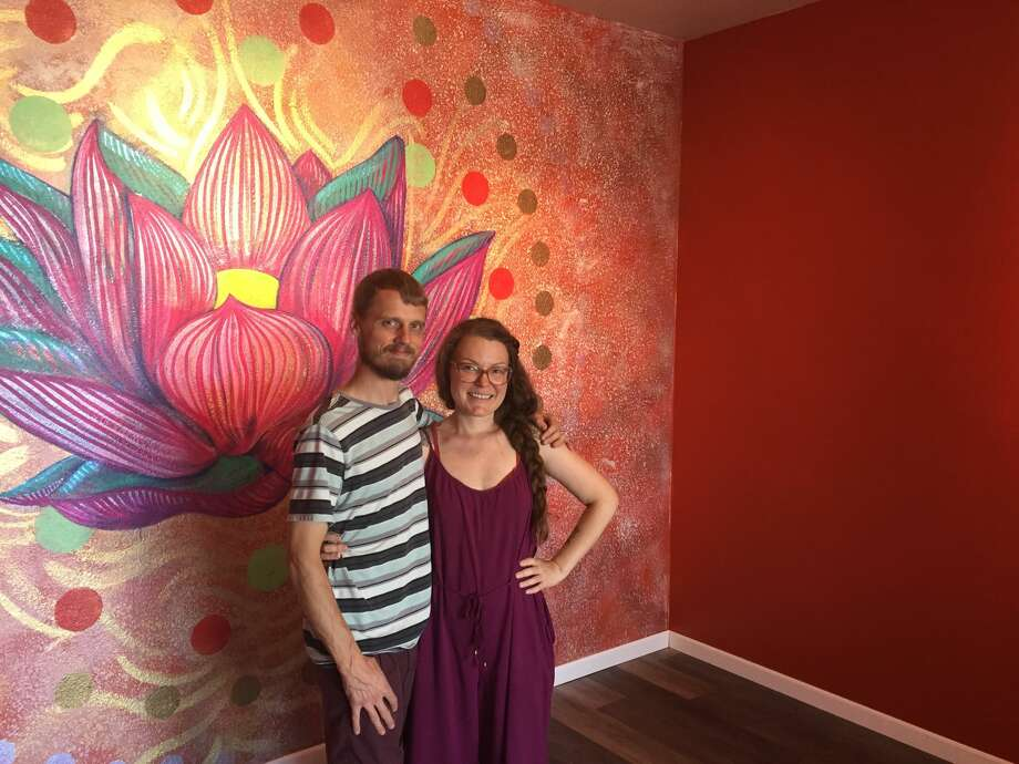 Scott and Kasie Lunson stand in the Sun Room getting ready for the opening of their new art and yoga studio on Saturday.