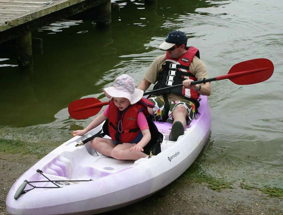 Daniel Renfrey and Zoe Renfrey return to the pier after spending a part of their afternoon paddling in Lake Livingston.  Kayaking was one of many camping activities that Texas Outdoor Family participants learned and enjoyed on Saturday, April 2, and Sunday, April 3, at Lake Livingston State Park.  Texas Outdoor Family is a program designed to teach families how to fish, kayak, cook out, set up a tent and base camp, and many other activities for $65 per family.  The overnight Texas Parks and Wildlife Department program is conducted at numerous state parks. Photo: STEPHEN THOMAS / The Advocate / The Advocate
